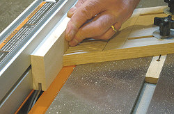 Building cabinet doors - Making the first pass over the blade to cut the groove.
