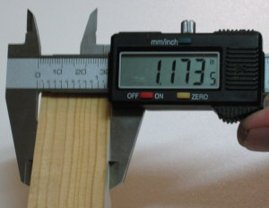 Using the digital calipers to measure the width of a piece of stock.
